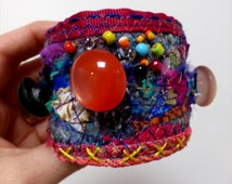 Carnival - Fabric Mayhem wide Cuff with mixed fabric, bold button decorations and press stud closure