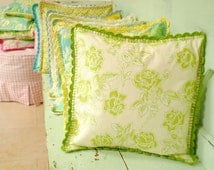 Cushion cover trimmed with a crochet edge in green and creams roses floral fabric