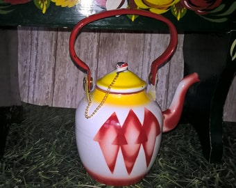 Brightly coloured enamel kettle. Red, yellow and white.