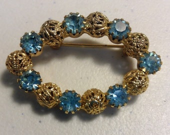 Gold tone filigree with light blue topaz pin