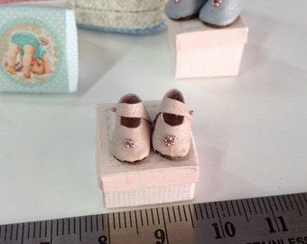 Miniature pink baby shoes. Dollhouse. Dusty pink baby shoes