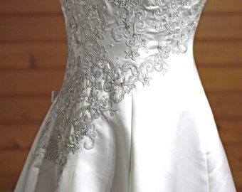New haute couture by Maggie Sottero white/silver wedding gown size 10-12 with spaghetti straps, lots of embroidery and sparkling crystals.