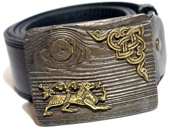 leather belt with a bronze buckle in the shape of an old tree with an ornament of a wolf