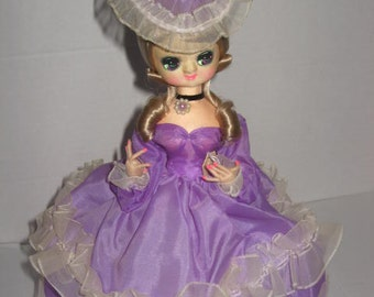 Lacy, dressed in purple,11 inch doll, feet glued to stand