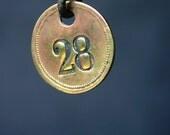 Twenty-eight. Vintage hotel room numbered golden tag.