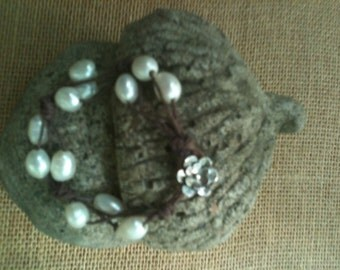Bracelet of white fresh water pearls and brown waxed linen.