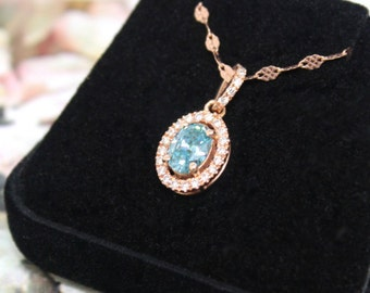 Oval Blue Diamond halo pendant in 14k rose gold