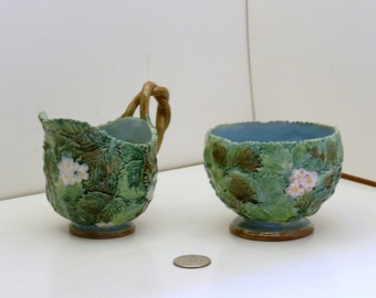 George Jones Majolica Sugar Bowl and Creamer that feature strawberry leaves and flowers.