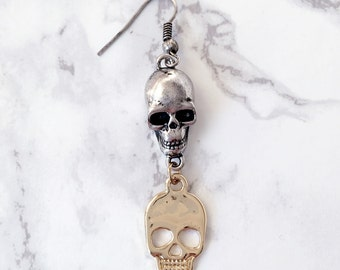 Earring in guld and silver with skulls.