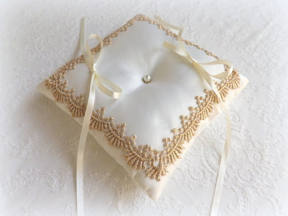 Ring Bearer. Ivory wedding ring pillow decorated with gold lace.