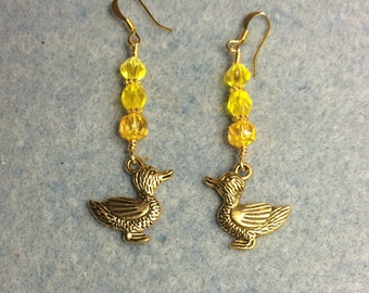 Gold duck charm dangle earrings adorned with yellow Czech glass beads.