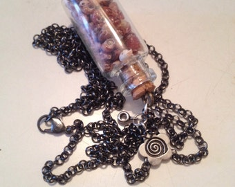 Necklace with glass bottle with pink at smallest possible speed.