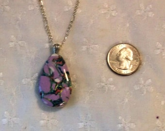 Pendant in Patchwork Pattern. Colors are green, lavender, white. Silver chain, resin finish