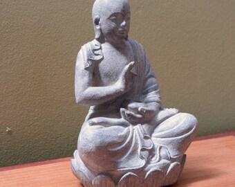 Vitarka monk on lotus made of volcanic ash