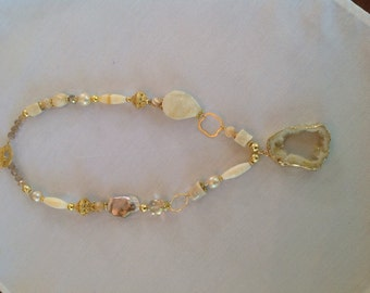 Gold wrapped ivory druzy quartz pendant on strand of a variety of beads including bamboo coral, pearls and orange calcite.