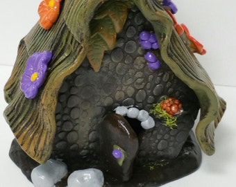 Ceramic Fairy House enhanced with pops of color and bits of moss