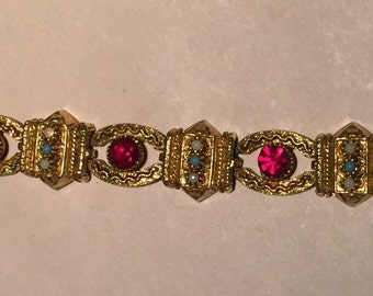 ART Egyptian Revival gold tone bracelet with ruby colored rhinestones