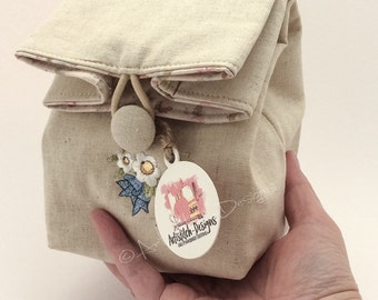 Mini linen cosmetic sack featuring machine embroidery design
