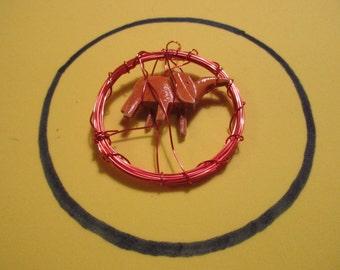 Orange wire wrapped around an elephant, pendant