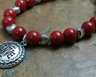 Red beaded bracelet with Love charm