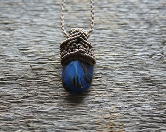 Single pendant with natural seed in macrame