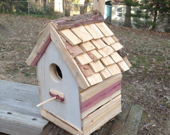 Small white with shingle roof single chamber birdhouse