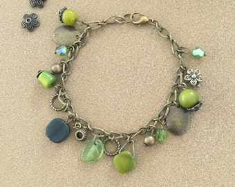 Charm bracelet in bronze metal and green beads of Crystal, glass, ivory Vegeta and peridot.