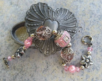 Adorable pink and silver bracelet with flower accents. This is absolutely darling.