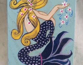 Blonde mermaid with handful of flowers
