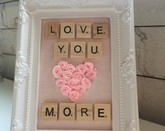 Love you more spelt inscrabble tiles in an ornate white frame!