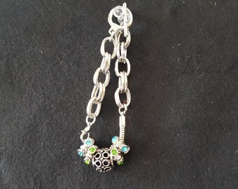 Black metal bead with multi-crystals surrounding.  The bracelet is silver double link with a toggle closure.