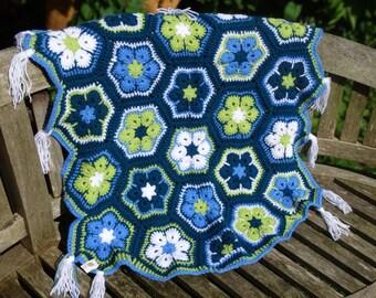 A gorgeous crocheted African flower stroller quilt