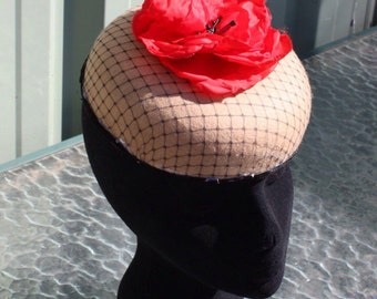 Camel pillbox hat ,  this smart felt hat is decorated with a large red  silk poppy and black net