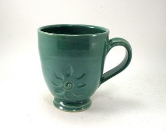 green mug with a flower