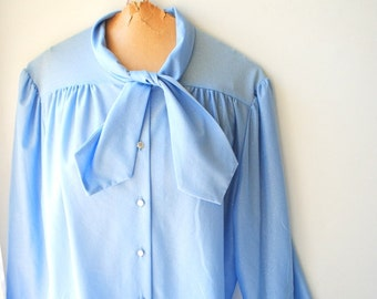 Classy vintage 70s pastel blue, thick textured polyester, secretary blouse with a high collar- tie. Made by Separate Scene. Size Large.