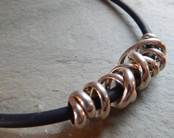 Sterling Silver Mumbo Jumbo Necklace, swirled sterling silver on black rubber cord, half round sterling silver wrap