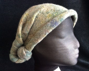 The knotted cloche style hat, made of hand dyed merino wool, wet felted and hand sculpted.