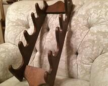 Wooden Gun Rack. Riffle Gun Display Holders Five Guns. The Best Load Gets The Most Game. Elegant Dark Wooden Gun Decor