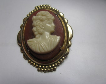 resin cameo on gold tone plaque setting. 1.5 inches.