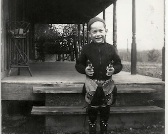 Old Photo Boy wearing Cowboy Gear holding 2 Guns 1930s Adirondack Table on Porch Photograph snapshot vintage