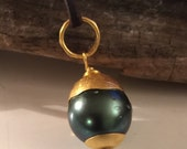 Gorgeous round black tahitian pearl set into 22k and 24k gold hangs from aussie leather cord. By ann biederman