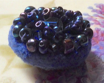 Beaded button, vintage.  Blue with purple/turqoise glow lustre beads & blue bugle beads with lustre beads attached, leather rev.  c 1940's.,