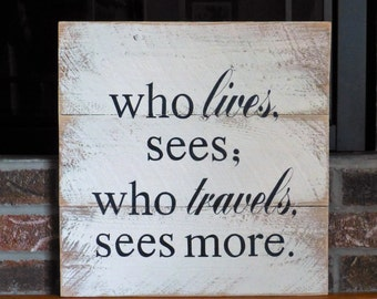 Who lives, sees; who travels, sees more sign, handpainted on reclaimed pallet wood.