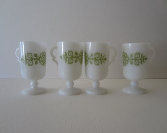 A set of 4 White Milk Glass Pedestal Mugs with a Mod Green Floral Motif
