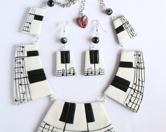 Set of necklace and earrings piano with sheet music.