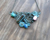 Openwork colorful necklace with a blue patina, flowers, pink, green, blue