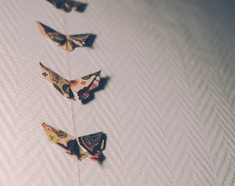 Origami garland of night butterflies in beige, brown and purple
