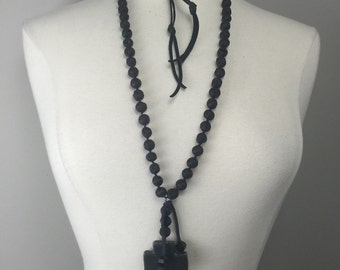 Hand knotted Black Lava beads with adjustable black leather ties and large black cross