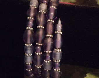 Purple glass beads with silver plated spacers on memory wire
