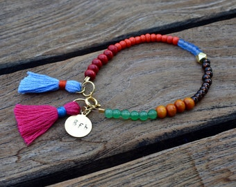 multi-colored, two tasseled, different beaded bracelet